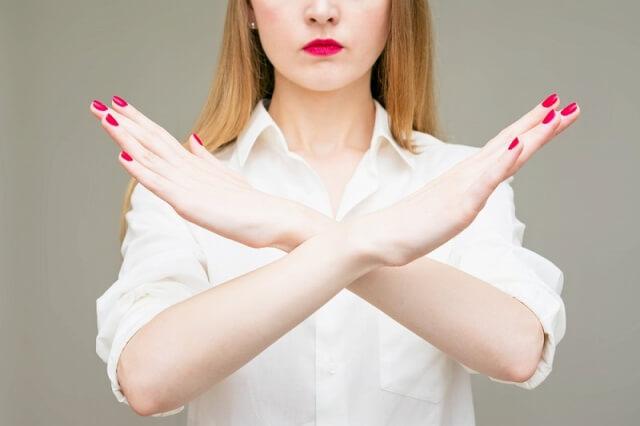 女性が両手でバツをしている