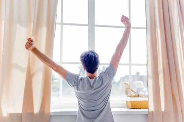 起きてカーテンを開けた日の光のさす窓にむかって両手を上げている男性