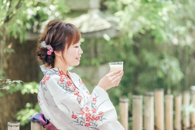 浴衣を着た女性がレトロな雰囲気のある庭でコップに入った甘酒を飲んでいる