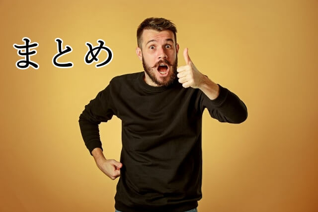 左手の親指を上げいいねポーズする髭の男性