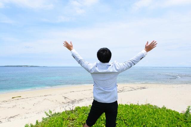 海岸で海に向かって手を広げて仰いでいる男性